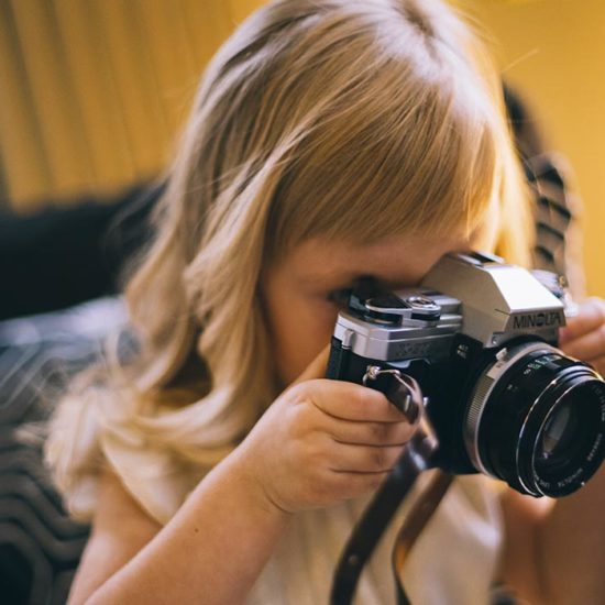 Bambina che scatta una fotografia con una reflex